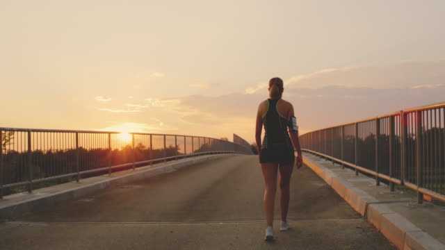 slo mo woman walking across a bridge at sunset - long hair stock videos & royalty-free footage