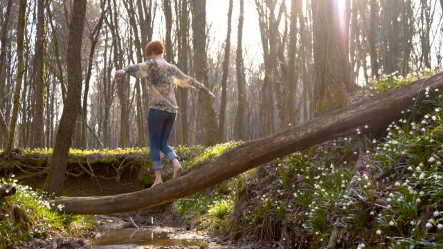 DS Frau zu Fuß auf einem Baumstamm im Wald