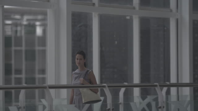 woman walking across a walk path inside a building with large window behind. - eurasian ethnicity stock videos and b-roll footage