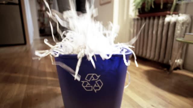 MS woman walking across apartment to recycle bin/ TD woman dropping shredded paper into bin/ woman picking up bin + walking away/ New York City