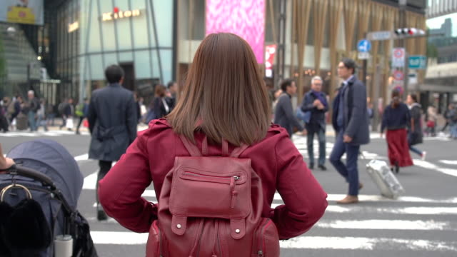 woman walking across crosswalk in ginza district, a famous luxurious shopping area in tokyo, japan - ginza stock videos & royalty-free footage