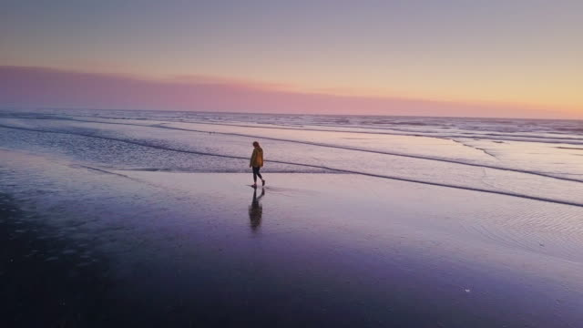 Woman Walking Alone on Beach at Sunset - Drone Shot