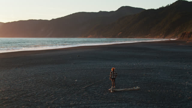 woman walking alone on remote beach at sunset - aerial - black sand stock videos & royalty-free footage