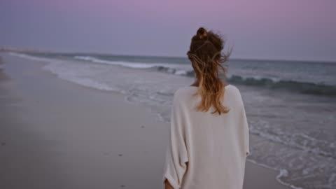 slo-mo-frau zu fuß an einem strand in der abenddämmerung - frauen stock-videos und b-roll-filmmaterial
