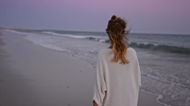 slo mo woman walking along a beach at dusk - grandangolo tecnica fotografica video stock e b–roll
