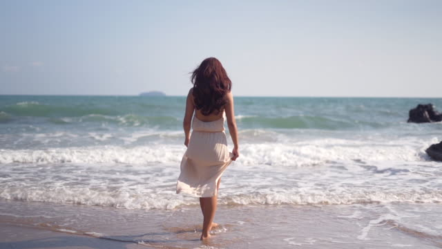 woman walking along a beach,young woman having fun splashing, happy girl walking at white sand tropical beach - female friendship stock videos & royalty-free footage