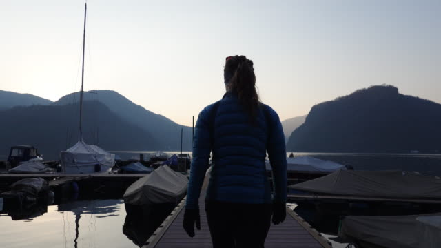frau läuft an einem dock bei sonnenuntergang vorbei an segelbooten - aktivitäten und sport stock-videos und b-roll-filmmaterial