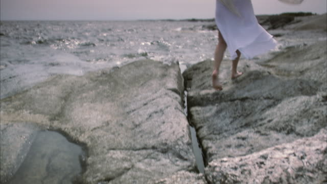 stockvideo's en b-roll-footage met a woman walking along a rocky shore huvudskar stockholm archipelago sweden. - mid adult men