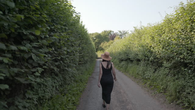 a woman walking along a single track road - somerset england stock videos & royalty-free footage