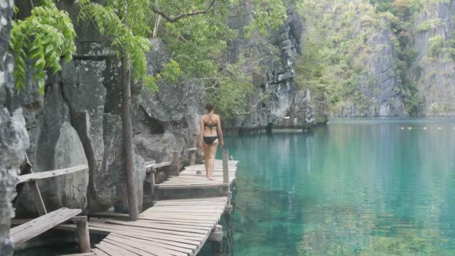 frau zu fuß entlang der promenade in privaten lagune - insel stock-videos und b-roll-filmmaterial