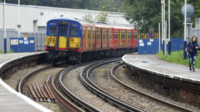ws woman walking along norbinton railway station platform, train leaving / london, england, united kingdom - bahnreisender stock-videos und b-roll-filmmaterial