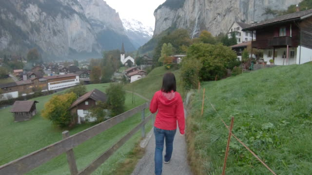 stockvideo's en b-roll-footage met vrouw wandelen langs het traject door dorp - alleen oudere vrouwen