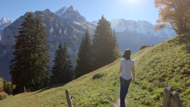 Woman walking along pathway with few mountain mountains across the valley