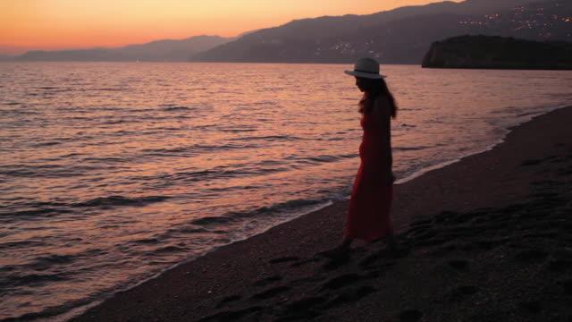vidéos et rushes de woman walking along the beach at dusk - robe rouge