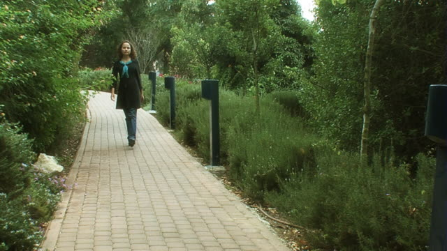 Woman walking along the pavement in park