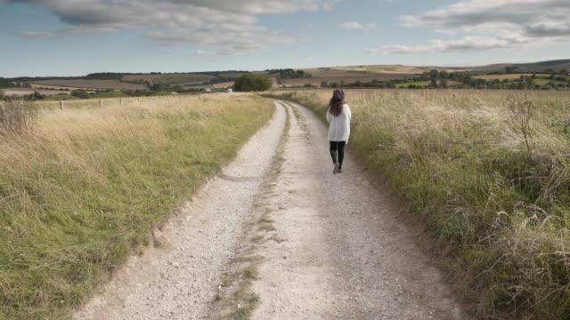a woman walking along the ridgeway near avebury an ancient trackway, britains oldest road - avebury stock videos & royalty-free footage