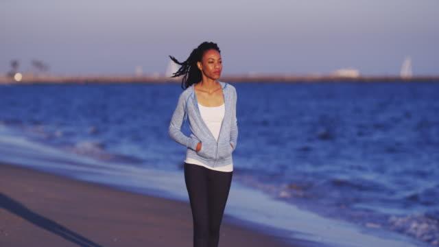 woman walking alongside the beach
