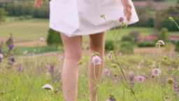 SLO MO R/F Woman walking among spring flowers swaying in the wind