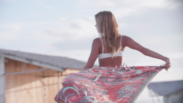 a woman walking and flirting, traveling in a bikini and sarong on a deck over water. - seductive women stock videos & royalty-free footage