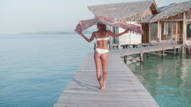 a woman walking and flirting, traveling in a bikini and sarong on a deck over water. - sarong stock videos & royalty-free footage