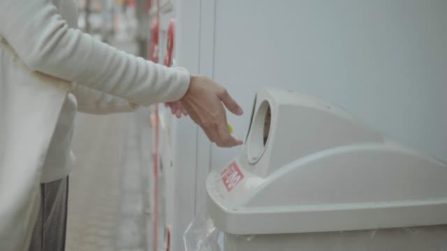 vídeos de stock e filmes b-roll de woman walking and throwing garbage to a trash bin - reciclagem