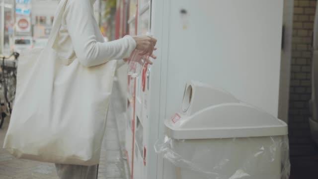 Woman walking and throwing garbage to a trash bin