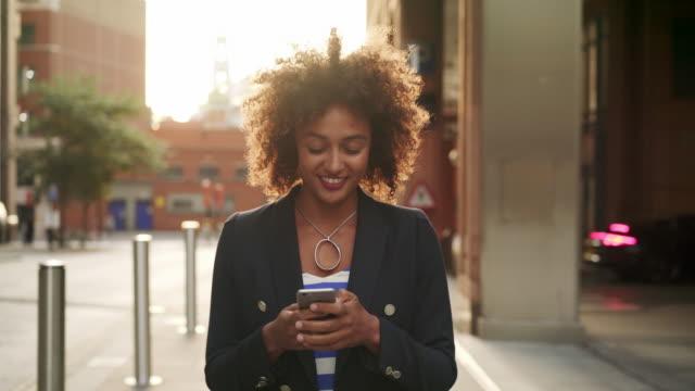 ts - woman walking and using smart phone at sunset, smiling - natural black hair stock videos & royalty-free footage
