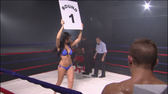 vídeos y material grabado en eventos de stock de ws woman walking around boxing ring with round 1 sign while trainers and referee assist boxer in corner / jacksonville, florida, usa - número 1