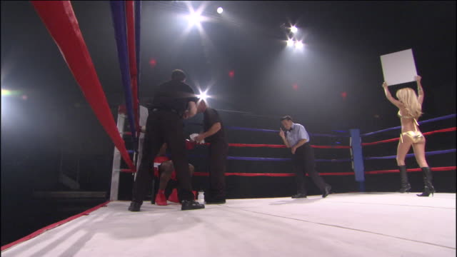 LA WS Woman walking around boxing ring with Round 5 sign while trainers and referee assist boxer in corner / Jacksonville, Florida, USA