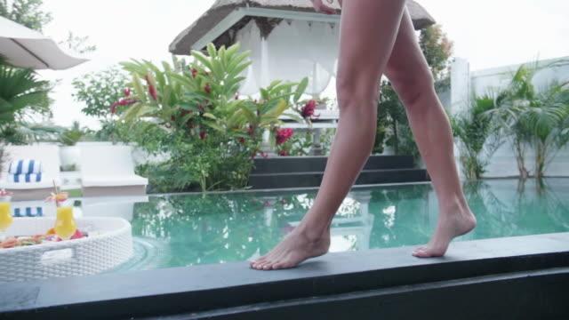 a woman walking at a pool at a resort hotel pool traveling in exotic tropical bali, indonesia. - slow motion - リゾート点の映像素材/bロール