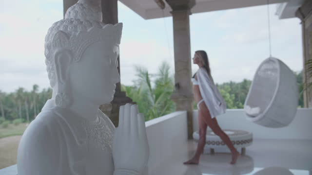 woman walking at a villa resort hotel with a buddha head, traveling in exotic tropical bali, indonesia. - slow motion - buddha stock videos & royalty-free footage
