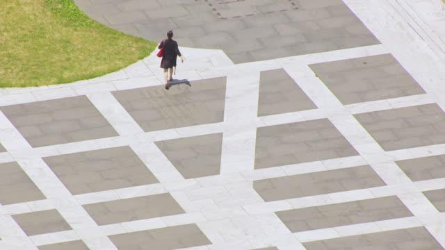WS AERIAL POV TS Woman walking at Freedom Plaza / Washington DC, United States