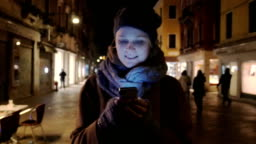 Woman walking at night and chatting on cell phone