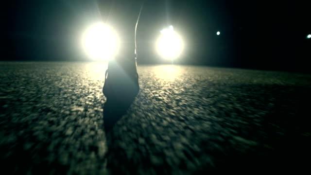 vídeos y material grabado en eventos de stock de mujer caminando por la noche frente a la luz del coche - coche deportivo