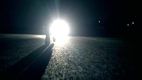 車のライトの前に夜を歩く女 - 路地点の映像素材/bロール