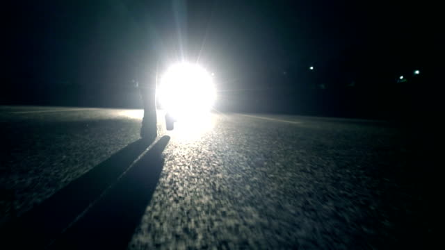 woman walking at night in front of car light - fanale anteriore video stock e b–roll