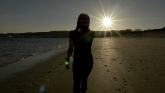 Woman walking at the beach with camera following her