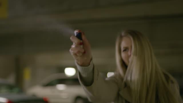 Woman walking backwards and spraying mace in parking garage / Provo, Utah, United States