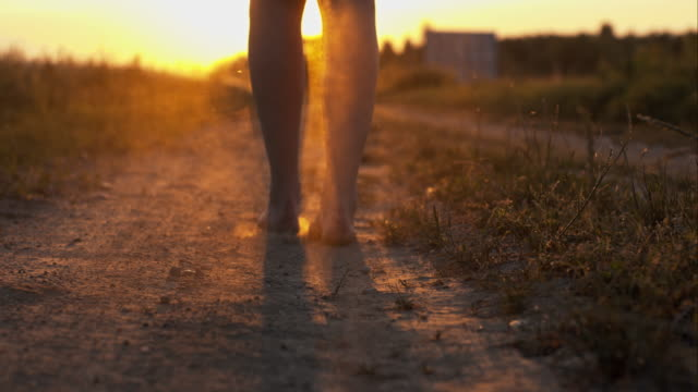 stockvideo's en b-roll-footage met woman walking barefoot on a dirt road - blootvoets