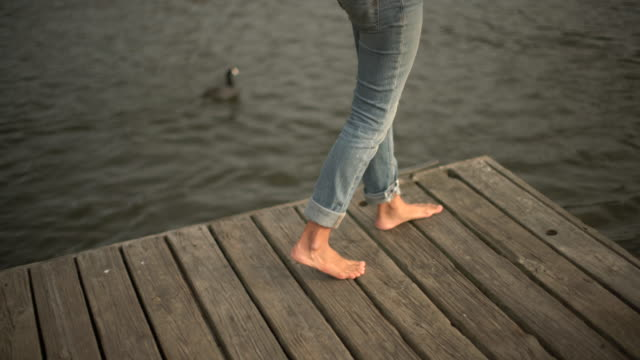 cu woman walking barefoot on a wooden pier - barefoot点の映像素材/bロール