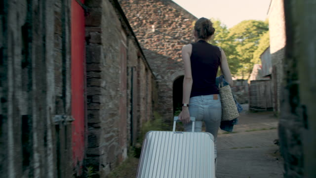 woman walking between buildings at country hotel - luggage stock videos & royalty-free footage