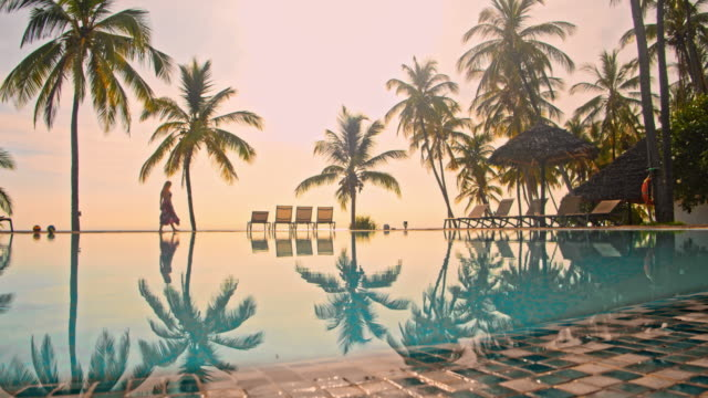 ws woman walking by the pool of a luxury resort - tropical tree stock videos & royalty-free footage