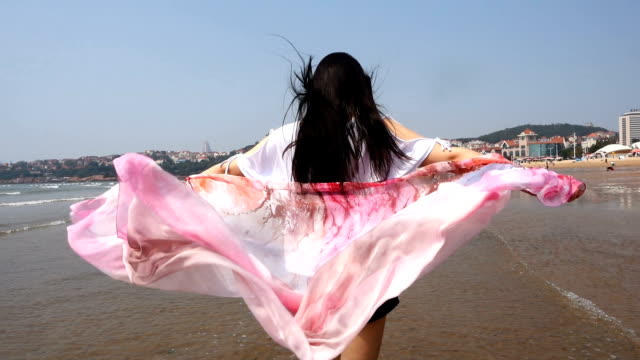 woman walking by the sea with scarf - sarong stock videos and b-roll footage