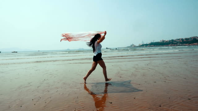 woman walking by the sea with scarf - sarong stock videos & royalty-free footage