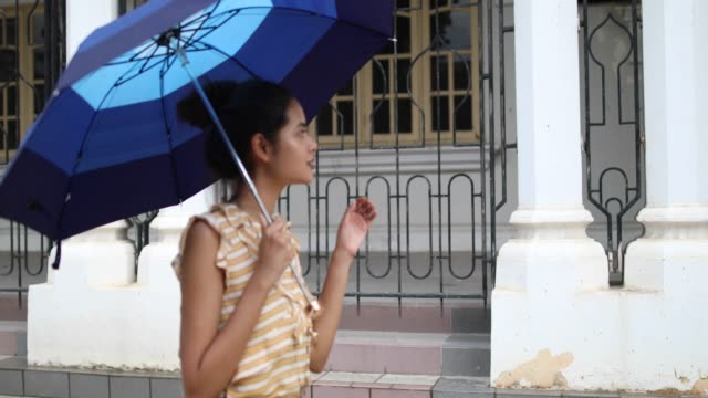 woman walking by the sultan abdul samad building, on a rainy day - cultura malesiana video stock e b–roll