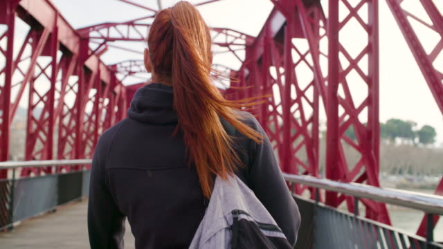 woman walking confident with a sport bag - brücke stock-videos und b-roll-filmmaterial