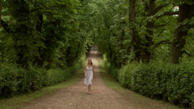 a woman walking down a picturesque path - see other clips from this shoot 1150 stock videos and b-roll footage