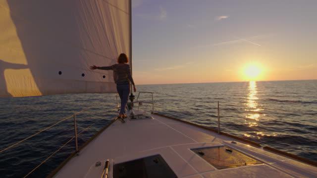 SLO MO Woman walking down a sailboat at sunset