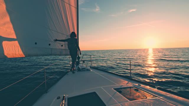 vídeos de stock, filmes e b-roll de ws mulher andando um veleiro ao pôr do sol - velejar