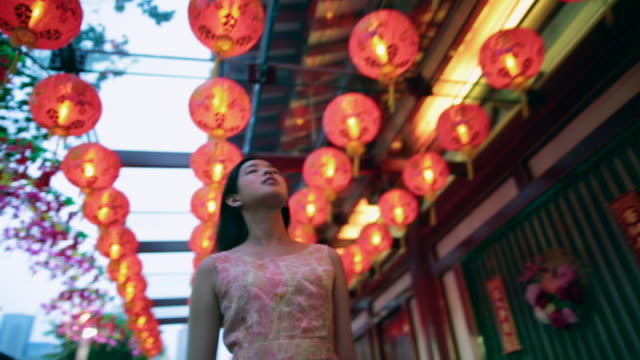 vídeos de stock, filmes e b-roll de ts woman walking down a street, under red lanterns, front view and rear view. - ano novo chinês